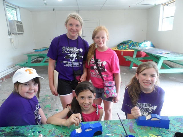 Summer Campers painting derby cars for group photo
